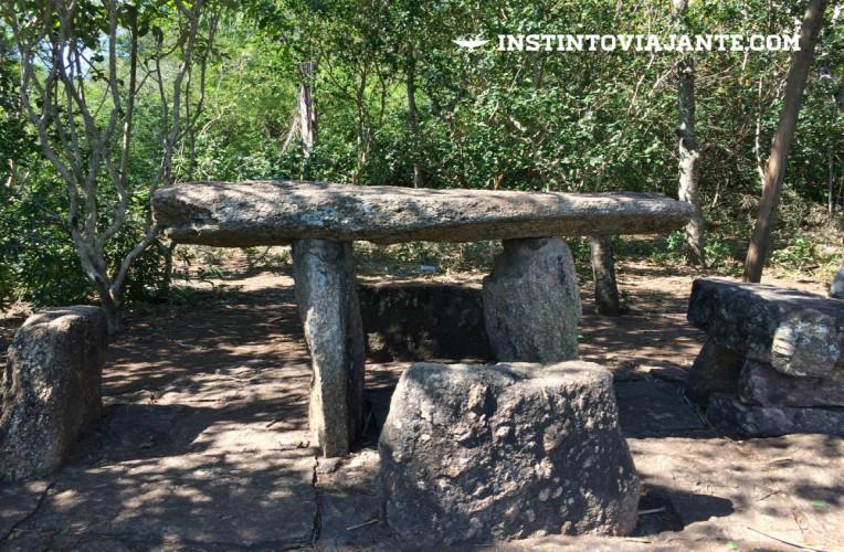 Bancos e mesas de pedra, sob sombras, que são ideais para descansar e fazer um piquenique.